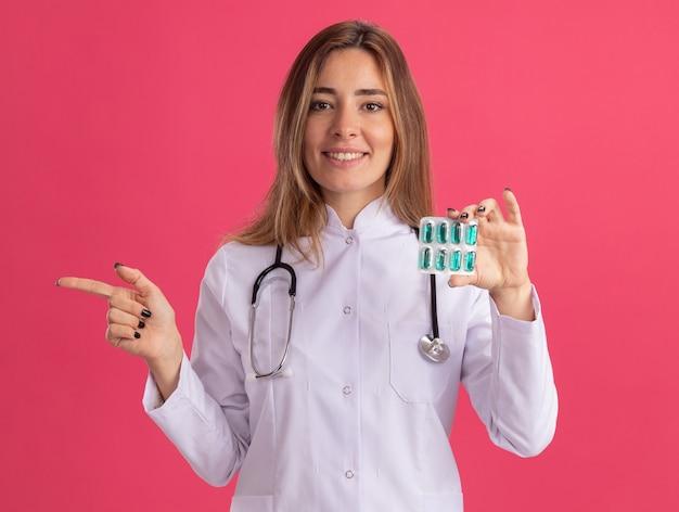 Uśmiechnięta młoda lekarka ubrana w szatę medyczną ze stetoskopem, trzymająca pigułki z boku na różowej ścianie
