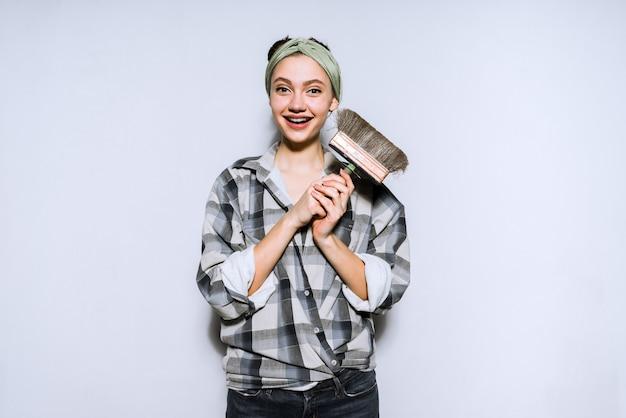 Uśmiechnięta młoda malarka trzymająca pędzel do malowania ścian i sufitu, naprawy