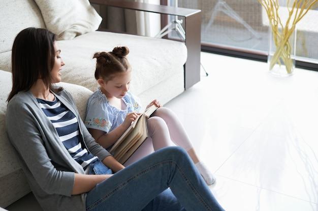 Uśmiechnięta młoda matka i córeczka siedzi na podłodze obok kanapy w domu i czyta książki.