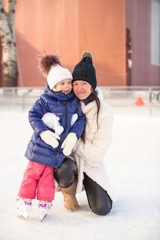 Uśmiechnięta młoda matka i jej słodkie córeczki na łyżwach razem