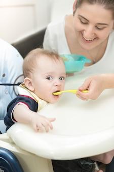 Uśmiechnięta młoda matka karmi swoje dziecko w krzesełku