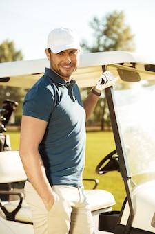 Uśmiechnięta młoda męska golfista pozycja przy golfową furą