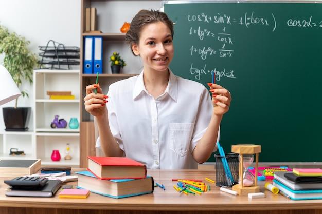 Uśmiechnięta młoda nauczycielka matematyki siedzi przy biurku z przyborami szkolnymi, trzymając kije liczące, patrząc na przód w klasie