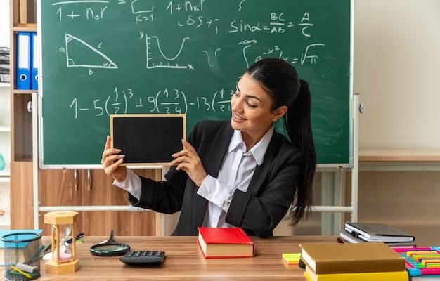 Uśmiechnięta młoda nauczycielka siedzi przy stole z narzędziami szkolnymi, trzymając i patrząc na mini tablicę w klasie