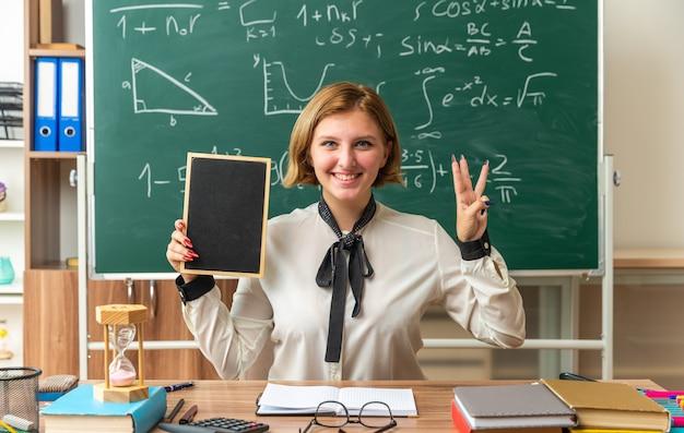 Uśmiechnięta młoda nauczycielka siedzi przy stole z przyborami szkolnymi, trzymając mini tablicę pokazującą trzy w klasie