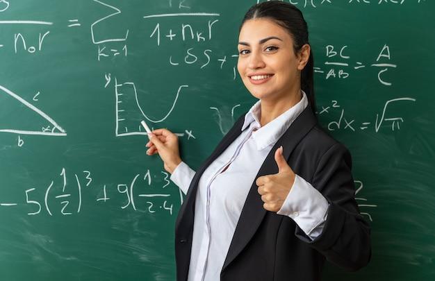 Uśmiechnięta młoda nauczycielka stojąca przed tablicą trzymająca się wyrzucona na tablicę pokazującą kciuk w klasie