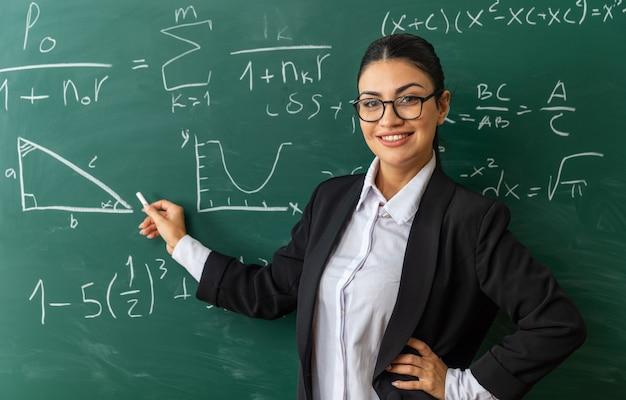Uśmiechnięta młoda nauczycielka w okularach stojąca przed tablicą trzymająca się wyrzucona na deskę, kładąc rękę na biodrze w klasie