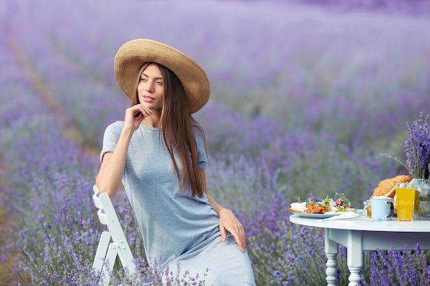 Uśmiechnięta młoda oszałamiająca kobieta pozuje w lawendowym polu