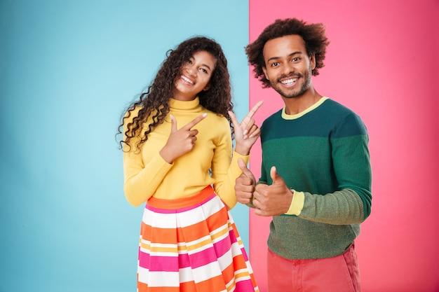 Uśmiechnięta młoda para afroamerykanów pokazująca kciuk w górę