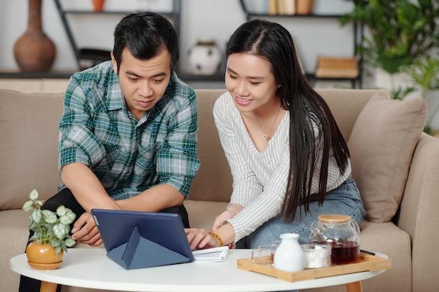 Uśmiechnięta młoda para azjatów pije herbatę i wybiera wideo do obejrzenia na tablecie w domu