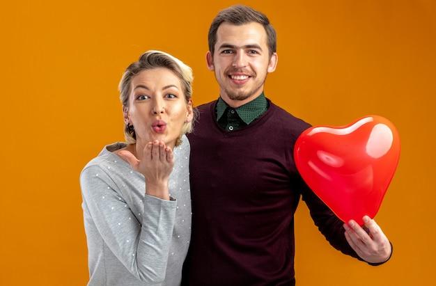 Uśmiechnięta młoda para na walentynki faceta trzymającego balonową dziewczynę w kształcie serca pokazującą gest pocałunku na białym tle na pomarańczowym tle