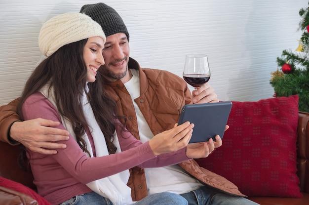 Uśmiechnięta młoda para odpoczywa i ogląda wideo na kanapie w salonie