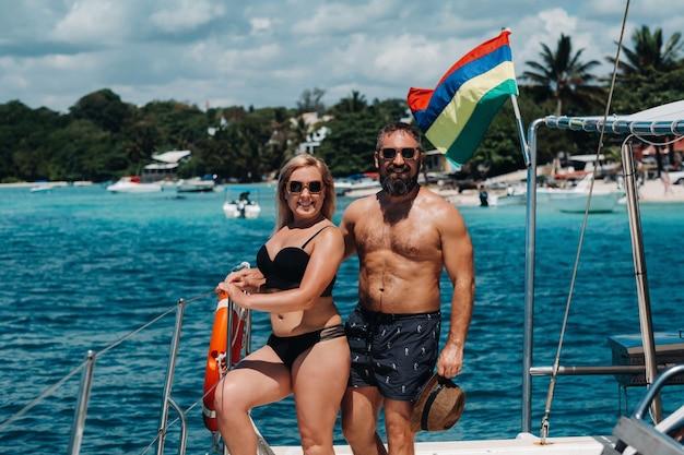 Uśmiechnięta młoda para patrząc na siebie, stojąc na pokładzie jachtu.