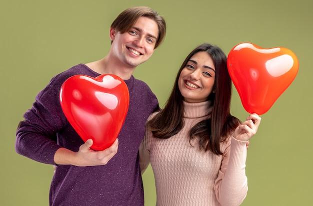 Uśmiechnięta młoda para patrząca na kamerę na walentynki trzymająca balony w kształcie serca na oliwkowo-zielonym tle