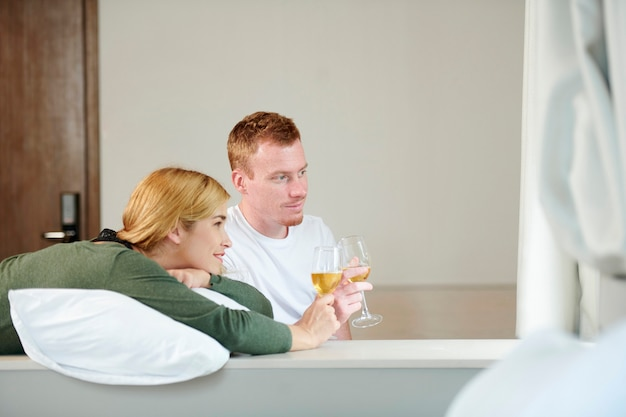 Uśmiechnięta młoda para pije szampana i ogląda film lub program telewizyjny