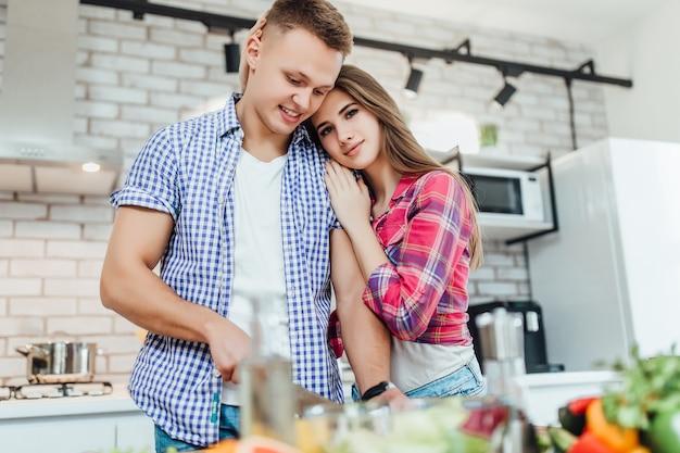 Uśmiechnięta młoda para przygotowuje obiad. mężczyzna kroi warzywa nożem, kobieta obejmuje jego od tyłu.