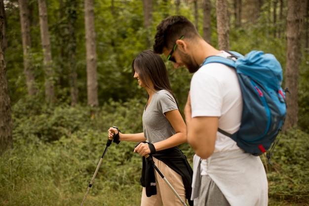 Uśmiechnięta młoda para spaceru z plecakami w lesie