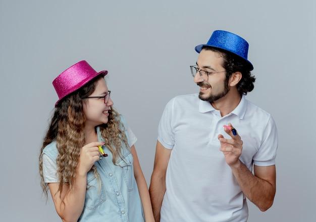 Uśmiechnięta młoda para ubrana w różowe i niebieskie kapelusze patrzą na siebie i trzymając gwizdek na białym tle