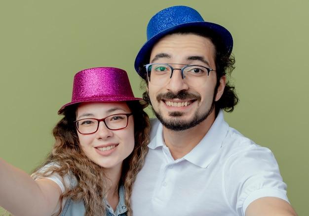 Uśmiechnięta młoda para ubrana w różowy i niebieski kapelusz trzymając aparat na białym tle na oliwkowej zieleni