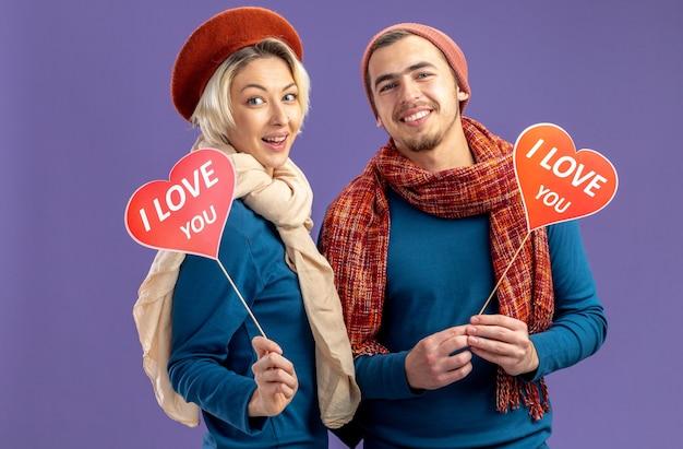 Uśmiechnięta młoda para w kapeluszu z szalikiem na walentynki trzymająca czerwone serca na patyku z tekstem kocham cię na białym tle na niebieskim tle