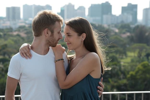 Uśmiechnięta młoda para zakochanych przytulających się i patrzących na siebie stojąc na dachu wysokiego budynku...