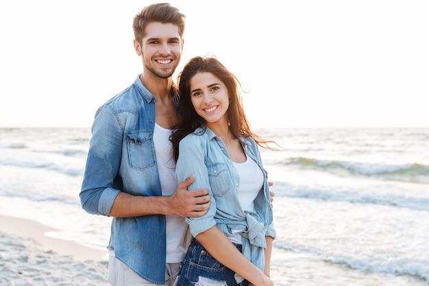 Uśmiechnięta młoda para zakochanych przytulających się na plaży