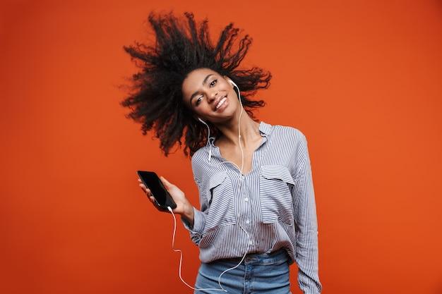 Uśmiechnięta młoda piękna afrykańska kobieta nosząca zwykłe ubrania stojąca na białym tle nad czerwoną ścianą, słuchająca muzyki przez słuchawki i telefon komórkowy, tańcząca