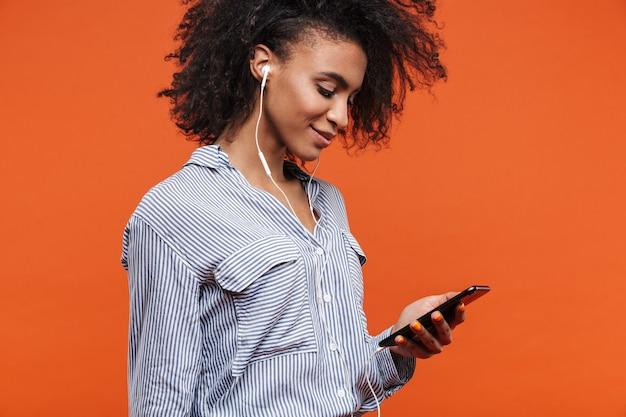 Uśmiechnięta młoda piękna afrykańska kobieta nosząca zwykłe ubrania, stojąca na białym tle nad czerwoną ścianą, słuchająca muzyki przez słuchawki i telefon komórkowy