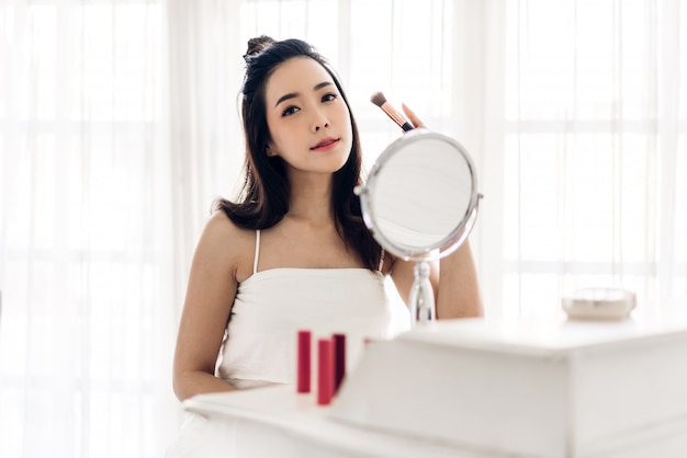 Uśmiechnięta młoda piękna azjatycka kobieta świeża zdrowa skóra patrząc na lustro i trzymając pędzle do makijażu z kosmetykami ustawionymi w domu