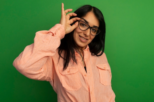 Uśmiechnięta młoda piękna dziewczyna na sobie różową koszulkę na sobie i trzymając okulary na białym tle na zielonej ścianie