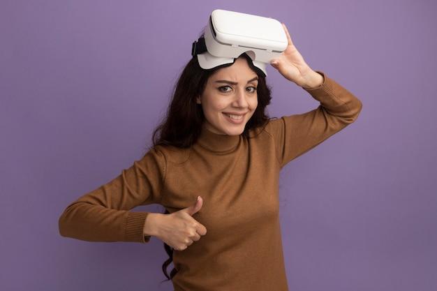 Uśmiechnięta młoda piękna dziewczyna nosi i trzyma zestaw słuchawkowy vr pokazując kciuk do góry na białym tle na fioletowej ścianie