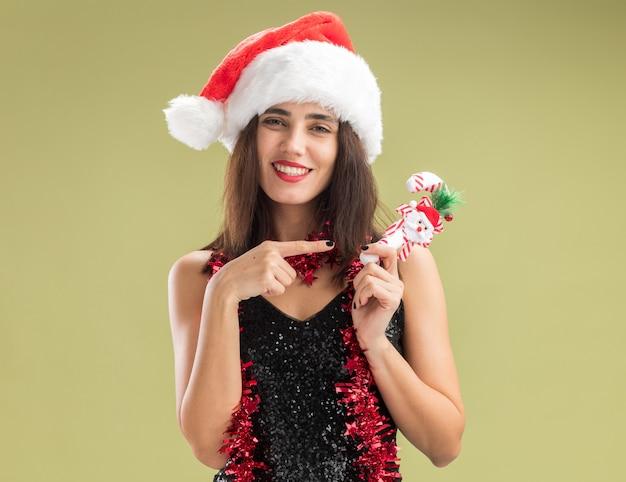 Uśmiechnięta młoda piękna dziewczyna nosi świąteczny kapelusz z girlandą na szyi i wskazuje na świąteczną zabawkę odizolowaną na oliwkowozielonym tle