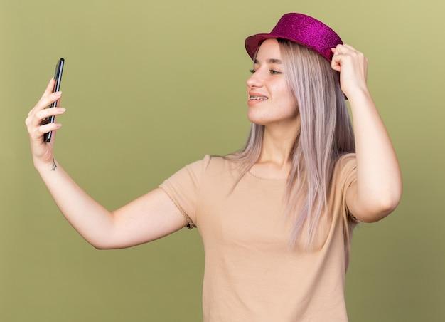 Uśmiechnięta młoda piękna dziewczyna nosząca aparat ortodontyczny i imprezowy kapelusz trzymający i patrzący na telefon odizolowany na oliwkowozielonej ścianie