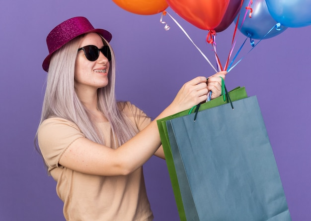 Uśmiechnięta młoda piękna dziewczyna nosząca aparat ortodontyczny i imprezowy kapelusz w okularach, trzymająca balony z torbą na prezenty odizolowaną na niebieskiej ścianie