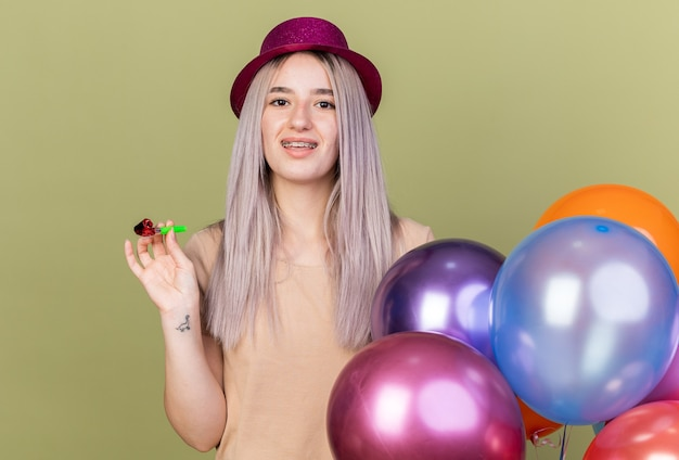 Uśmiechnięta młoda piękna dziewczyna nosząca aparat ortodontyczny z imprezowym kapeluszem stojącym w pobliżu balonów, trzymająca gwizdek imprezowy odizolowany na oliwkowozielonej ścianie