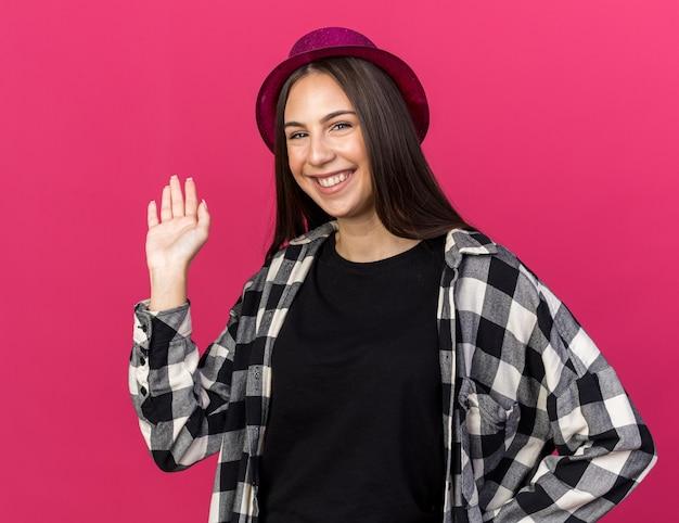 Uśmiechnięta młoda piękna dziewczyna nosząca imprezowy kapelusz wskazuje ręką za odizolowaną na różowej ścianie z miejscem na kopię