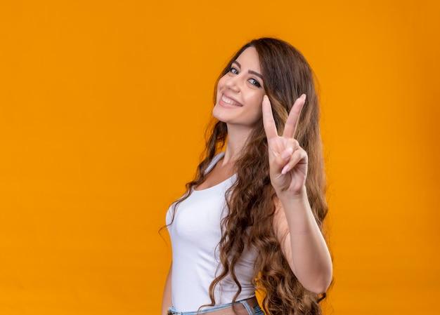 Uśmiechnięta młoda piękna dziewczyna robi znak pokoju stojąc w widoku profilu na odizolowanych pomarańczowej przestrzeni z miejsca na kopię