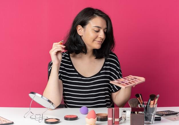 Uśmiechnięta młoda piękna dziewczyna siedzi przy stole z narzędziami do makijażu, trzymając i patrząc na paletę cieni do powiek z pędzlem do makijażu na różowym tle