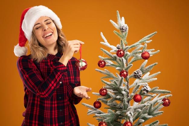 Uśmiechnięta młoda piękna dziewczyna stojąca w pobliżu choinki w świątecznym kapeluszu udekorować choinkę udekorować choinkę na pomarańczowym tle