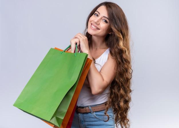 Uśmiechnięta młoda piękna dziewczyna trzyma torby na zakupy