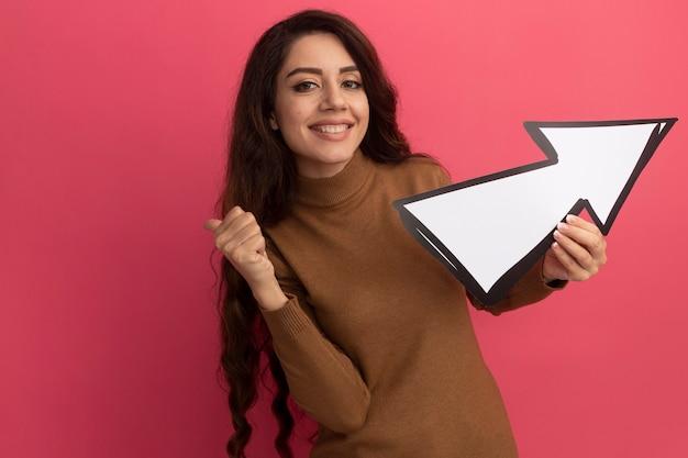 Uśmiechnięta młoda piękna dziewczyna trzyma znak kierunku ahowing kciuk w górę na białym tle na różowej ścianie