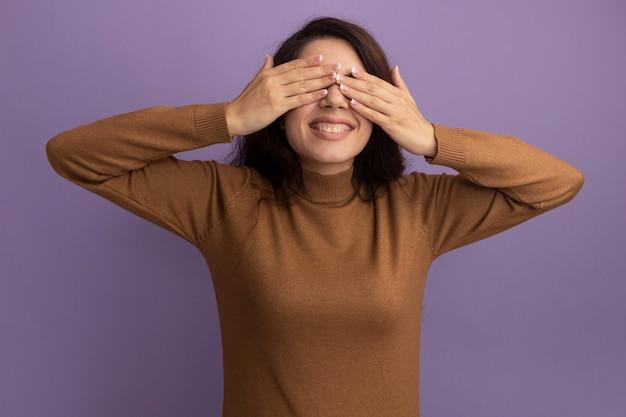 Uśmiechnięta młoda piękna dziewczyna ubrana w brązowy sweter z golfem zakryte oczy rękami odizolowanymi na fioletowej ścianie