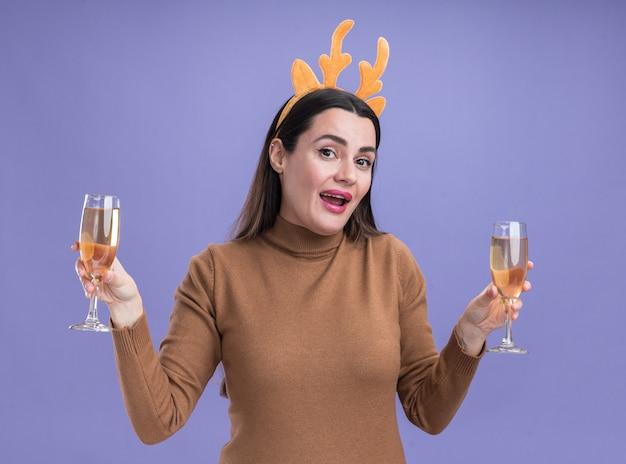 Uśmiechnięta młoda piękna dziewczyna ubrana w brązowy sweter ze świąteczną obręczą do włosów, trzymająca dwa kieliszki szampana odizolowane na niebieskiej ścianie