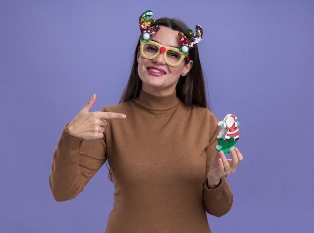 Uśmiechnięta młoda piękna dziewczyna ubrana w brązowy sweter ze świątecznymi okularami trzymająca i wskazująca na zabawkę odizolowaną na niebieskiej ścianie