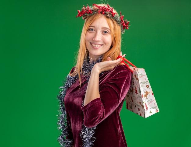 Uśmiechnięta młoda piękna dziewczyna ubrana w czerwoną sukienkę z wieńcem i girlandą na szyi trzymającą torbę z prezentami na ramieniu odizolowaną na zielonej ścianie