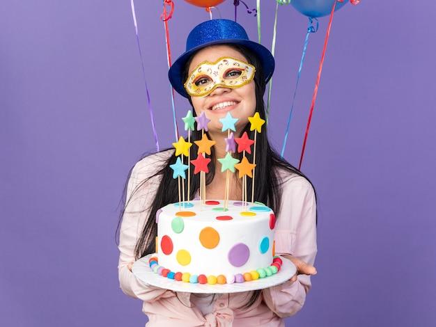 Uśmiechnięta młoda piękna dziewczyna ubrana w imprezowy kapelusz i maskę na oczy, stojąca przed balonami i trzymająca ciasto izolowane na niebieskiej ścianie