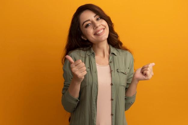 Uśmiechnięta młoda piękna dziewczyna ubrana w oliwkową koszulkę pokazując kciuki do góry na białym tle na żółtej ścianie