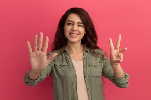 Uśmiechnięta młoda piękna dziewczyna ubrana w oliwkowozieloną koszulkę przedstawiającą różne numery na białym tle na różowej ścianie