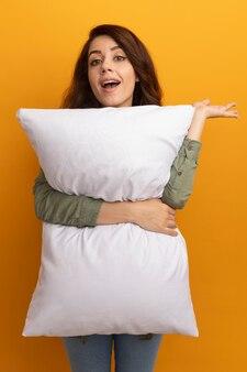 Uśmiechnięta młoda piękna dziewczyna ubrana w oliwkowozieloną koszulkę przytuliła poduszkę, rozkładając rękę na białym tle na żółtej ścianie