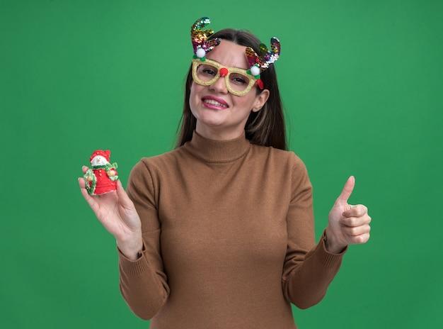 Uśmiechnięta młoda piękna dziewczyna w brązowym swetrze i świątecznych okularach trzymająca świąteczną zabawkę pokazującą kciuk na zielonej ścianie